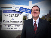 Roger J Turner in front of sold sign